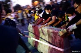 Anti-government protesters tear down barricades during demonstration outside Government House, Bangkok, Nov. 30, 2013.