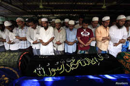 Muslims pray behind the coffins of victims of a fire during a funeral at Yaeway cemetery in Rangoon, April 2, 2013.