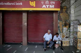 A security guard, right, reads a newspaper as he sits in front of a closed ATM in New Delhi, India, Wednesday, April 18, 2018. Several ATM's were seen to have run dry across the country, reportedly from a surge in demand of cash withdrawals.