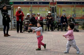 FILE - In this March 31, 2016, file photo, children play bubbles at a residential compound in Beijing.