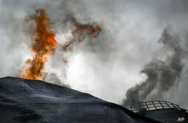 A fuel tank of a power station burns on the outskirts of the city of Ajdabiya, south of Benghazi, eastern Libya, March 21, 2011