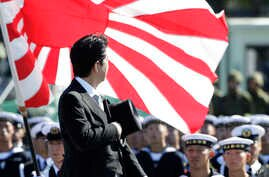Japanese Prime Minister Shinzo Abe reviews members of Japan Self-Defense Forces (SDF) during the Self-Defense Forces Day at Asaka Base, north of Tokyo, Sunday, Oct. 27, 2013.