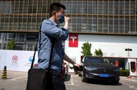 A man wears a mask as he walks past a Tesla electric vehicle showroom and charging station in Beijing, China, April 14, 2017.