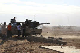 FILE - Fighters are seen firing a vehicle-mounted weapon on the outskirts of Sidra, Libya, Dec. 14, 2014.