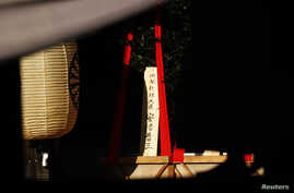 """A wooden sign reading """"Prime Minister Shinzo Abe"""" is seen on a ritual offering from the prime minister to the Yasukuni Shrine in Tokyo, October 17, 2014."""
