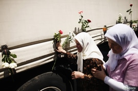 Bosnian women touches one of the three trucks carrying 520 coffins of newly identified victims of the 1995 Srebrenica massacre in front of the presidential building in Sarajevo July 9, 2012. The bodies of the recently identified victims will be trans...