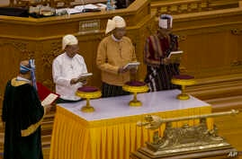 Htin Kyaw, second right, takes oaths as Myanmar's new president during a sworn-in ceremony in Myanmar's parliament in Naypyitaw, Myanmar, Wednesday, March 30, 2016.