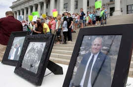 FILE - Family photographs of Joshua Holt, an American jailed in Venezuela, are part of a rally at the Utah State Capitol on July 30, 2016, in Salt Lake City. Holt was arrested on suspicion of weapons charges after he traveled to Venezuela on a touris