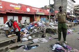A policeman secures the scene of twin explosions at the Gikomba open-air market for second-hand clothes in Kenya's capital Nairobi, May 16, 2014.