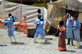 Health workers walk in an isolation center for people infected with Ebola at Donka Hospital in Conakry, April 14, 2014.