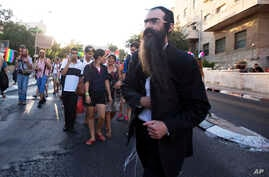 Ultra-Orthodox Jew Yishai Schlissel walks through a Gay Pride parade and is just about to pull a knife from under his coat and start stabbing people in Jerusalem, July 30, 2015.
