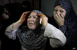 Palestinian mourners weep during the funeral of two-year-old, Rahaf Hassan, and her 30-year-old pregnant mother, Noor Hassan, who were killed in an Israeli air strike Sunday morning, during their funeral in the family house south of Gaza city in the