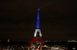 The Eiffel Tower is illuminated in the French national colors red, white and blue in honor of the victims of the terror attacks last Friday in Paris, Monday, Nov. 16, 2015.