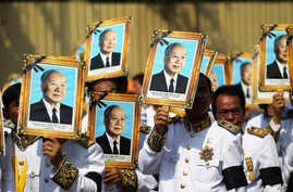 Procession participants shield themselves from the sun with portraits of the late former Cambodian King Norodom Sihanouk in a funeral procession in Phnom Penh, February 1, 2013.