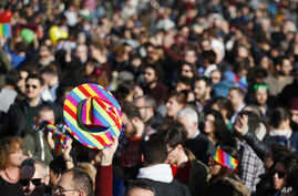 FILE - People are seen at a gay rights rally prior to a vote at the Italian parliament to change laws on recognition of rights for same-sex couples, in downtown Milan, Italy, Feb. 21, 2016.