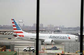 FILE - In a March 13, 2019 file photo, an American Airlines Boeing 737 MAX 8 sits at a boarding gate at LaGuardia Airport in New York. American Airlines said Sunday, April 7, 2019 it is extending by over a month its cancellations of about 90 daily fl