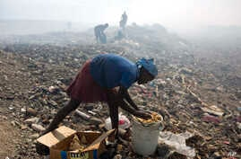 Nadia Prophete, 12, collects food from a trash to sell to pig owners at the Cite Soleil area of Port-au-Prince, Haiti, June 12, 2017.