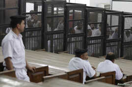 """Islamist defendants stand behind bars in the case known as the """"Kerdasa massacre'', that referred 188 people to court over an attack that killed 14 policemen last summer, in Cairo, Eygpt, June 23, 2014."""