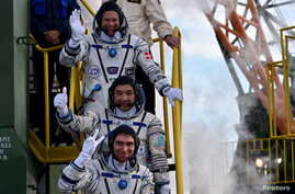 From top to bottom, Andreas Mogensen, Aydyn Aimbetov and Sergei Volkov wave as they board the Soyuz TMA-18M spacecraft at the Baikonur Cosmodrome, Sept. 2, 2015.