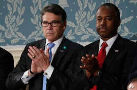 Rick Perry, left, and Ben Carson applaud on Capitol Hill in Washington, Feb. 28, 2017, before President Donald Trump's address to a joint session of Congress. Perry was confirmed as energy secretary and Carson as housing and urban development secreta