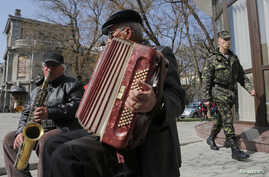A member of a pro-Russian self-defence unit walks past street musicians in the Crimean city of Simferopol April 7, 2014.