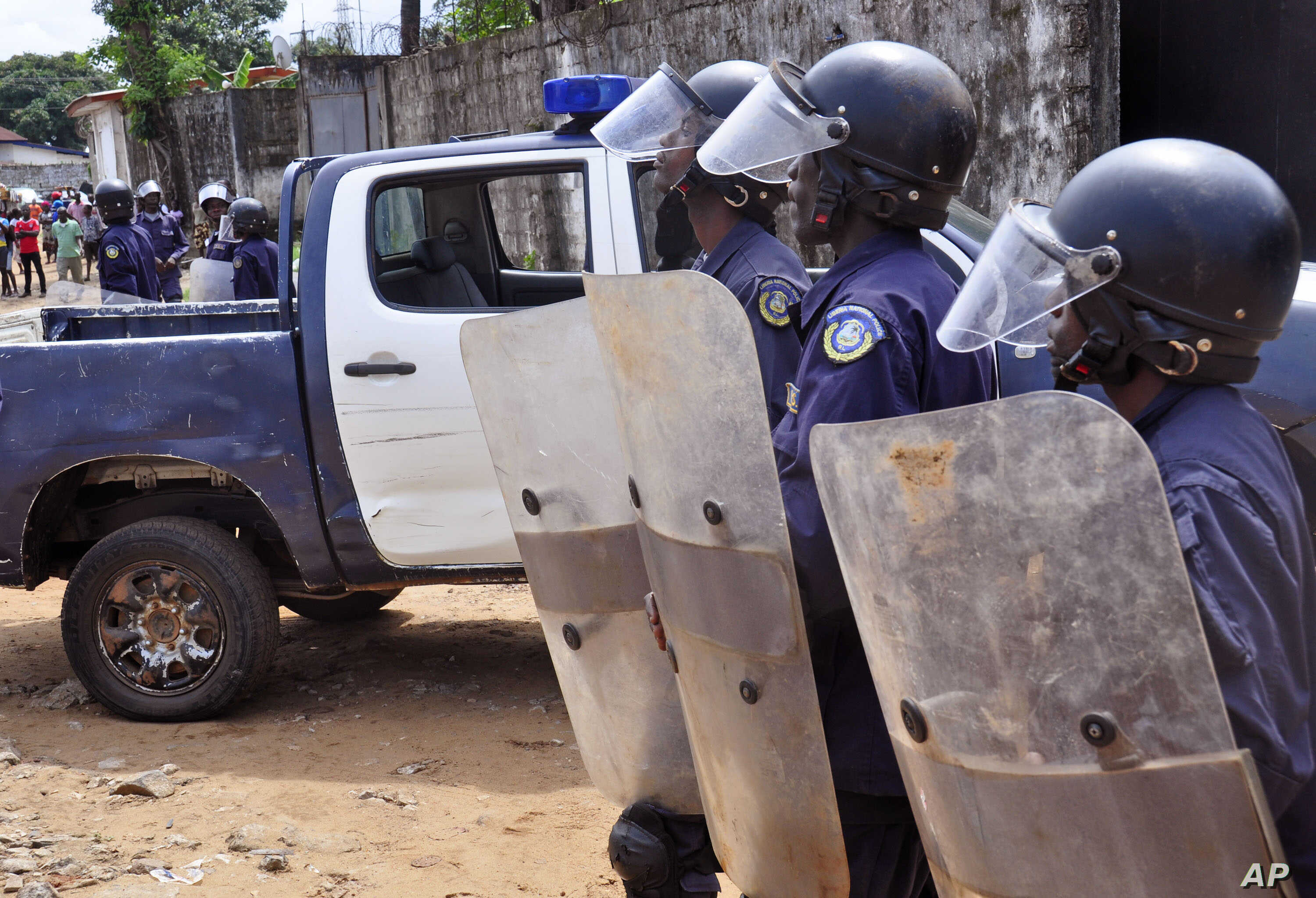 Liberian policemen, right, dressed in riot gear disperse a crowd of people that blocked a main road after the body of someone suspected of dying from the Ebola virus was not removed by health workers in the city of Monrovia, Liberia, Aug. 14, 2014.