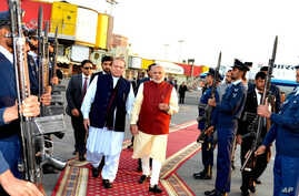 In this photo released by Press Information Department, India's Prime Minister Narendra Modi, right, reviews guard of honor with his Pakistani counterpart, Nawaz Sharif, in Lahore, Pakistan, Dec. 25, 2015.