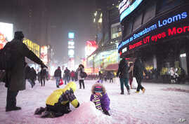 Children make a snow pile in Times Square, during a snowstorm, Thursday, Jan. 2, 2014, in New York.