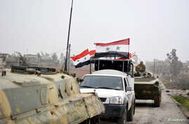 FILE - Fighters loyal to Syria's President Bashar Al-Assad ride on military vehicles and tanks after regaining control of Deir al-Adas, a town south of Damascus, Daraa countryside.