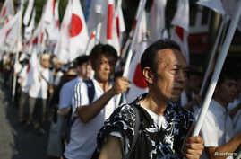 """Members of the nationalist movement """"Ganbare Nippon"""" holding Japanese national flags march while paying tribute to the war dead near Yasukuni Shrine in Tokyo, August 15, 2013, on the 68th anniversary of Japan's surrender in World War II."""