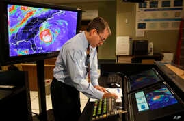 FILE - In this Sept. 2, 2010, file photo, Chief hurricane forecaster James Franklin prepares for a live update on Hurricane Earl at the National Hurricane Center in Miami. Franklin, a retiring chief of the hurricane specialist unit at the National Hu