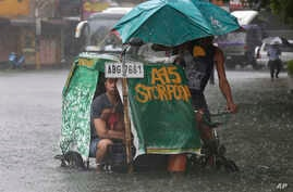 A Filipino man and his dog ride a pedicab along a flooded road in suburban Mandaluyong, east of Manila, Philippines, as monsoon downpours intensify while Typhoon Nepartak exits the country on Friday, July 8, 2016.