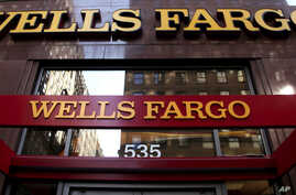 FILE - A Wells Fargo sign is displayed at a branch in New York.