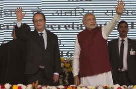 French President Francois Hollande, left, and Indian Prime Minister Narendra Modi wave at the audience as they arrive for the foundation stone laying for the headquarters of the International Solar Allliance at Gurgaon, outskirts of New Delhi, India,