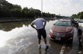Robert Briscoe checks the damage to his flooded car along Interstate 45 in Houston, May 26, 2015.