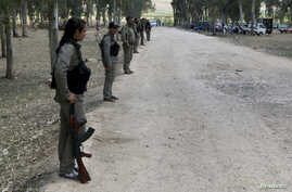 Kurdish Democratic Union Party (PYD) members stand guard during a Labour Day celebration in Efrin May 1, 2014