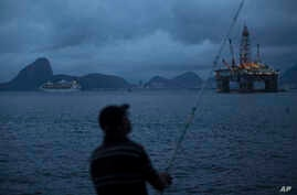 FILE - A man fishes in Guanabara Bay where an oil platform floats, backdropped by Sugar Loaf Mountain, left, in Niteroi, Brazil, April 21, 2015.