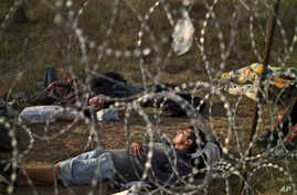 Afghan refugees sleep next to razor-wire barrier at the Serbian side of Hungary's border fence with Serbia, in Asotthalom, southern Hungary, Sept. 17, 2015. T