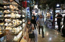 FILE - People walk through the Grand Bazaar where Chinese-made goods have flooded the market, in Tehran, Iran, Sept. 6, 2018. It's hard not to see China wherever you look in Iran. From Chinese goods to its business people eager for deals as Western b