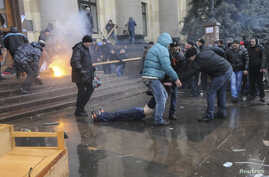Pro-Russian protesters drag a wounded man during clashes with supporters of Ukraine's new government in central Kharkiv March 1, 2014. Pro-Russia activists clashed with supporters of the new Ukrainian government in the eastern Ukrainian city of Khark