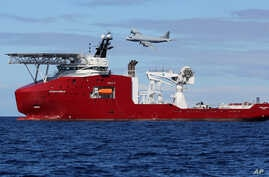 In this April 9, 2014 photo provided by the Australian Defense Force, a Royal Australian Air Force AP-3C Orion flies past Australian Defense vessel Ocean Shield on a mission to drop sonar buoys to assist in the acoustic search of the missing Malaysia