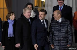 Britain's Foreign Secretary Boris Johnson and France's President Emmanuel Macron prepare for a group photo at the Royal Military Academy Sandhurst, during UK-France summit talks in Sandhurst, Britain, Jan. 18, 2018.