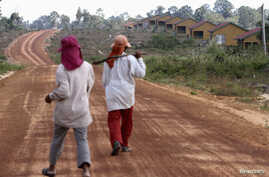 FILE - Women walk past houses, built for the residents being displaced by land sales, at Botum Sakor National Park in Koh Kong province, Feb. 20, 2012. About 200 families displaced by construction have returned to their homes, demanding more compensa