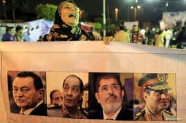A protester opposed tot the Egyptian army and government shouts slogans, holds a banner during a demonstration against the army and government at Abdeen square in downtown Cairo, Nov. 18, 2013.