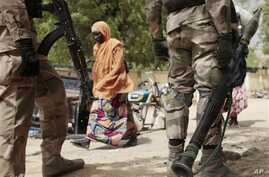 In this photo taken Wednesday, April 8, 2015, a woman walks past Nigerian Soldiers at a checkpoint in Gwoza, Nigeria, a town newly liberated from Boko Haram.   Each day brings new reports of atrocities, with mass graves being discovered in towns seiz