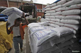 A laborer unloads sacks filled with rice at a wholesale grain market in the northern Indian city of Chandigarh, July 29, 2014.