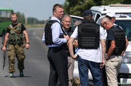 Alexander Hug (front C), deputy head for the Organization for Security and Cooperation in Europe's (OSCE) monitoring mission in Ukraine, stands with members of his team on the way to the MH17 crash site in eastern Ukraine, July 30, 2014.