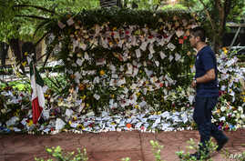 A man passes by messages placed in an offering to the victims of Mexico City's earthquake, Sept. 25, 2017.