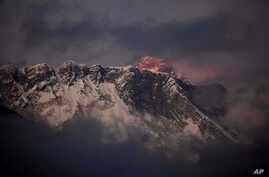 FILE - In this Oct. 27, 2011 file photo, the last light of the day sets on Mount Everest as it rises behind Mount Nuptse as seen from Tengboche, in the Himalaya's Khumbu region, Nepal.