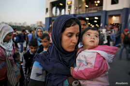 Syrian refugees disembark from a Greek ferry after arriving in the port of Piraeus near Athens, June 14, 2015.